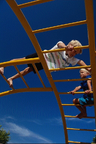 Two Children on a ladder at the playground.